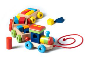 A wooden toy train carrying puzzle pieces as cargo, painted in many colors, pulled by a red string. Isolated on white background.